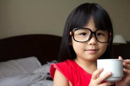 Portrait of a little girl wearing spectacles and hold a cup in hotel room Stock Photo