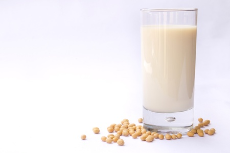 soymilk: Glass of soya milk surrounded by soya beans isolated on white background Stock Photo