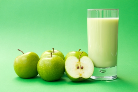 Fresh green apple yogurt drink surrounded by green apples