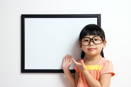 Niña de la escuela lleva una gafas de grandes posando junto a una pizarra blanca Foto de archivo - 13620141