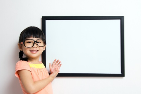 spectacle: School girl wears a big spectacles posing next to a white board