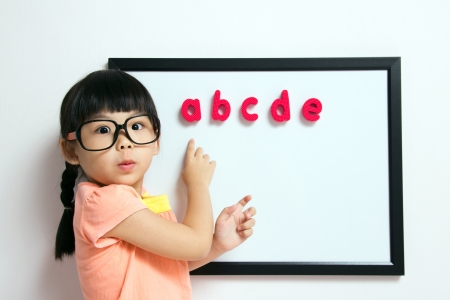 School girl wears a big spectacles posing next to a white board Stock Photo - 13620142