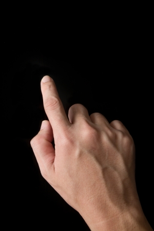 Index finger touching screen isolated on black background