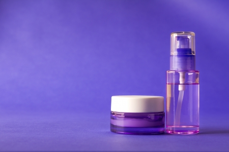 Purple cosmetic and beauty products on purple background photo