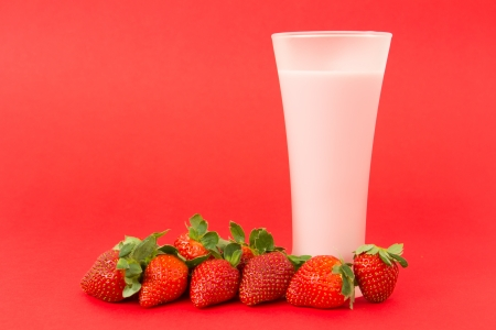 Fresh strawberry yogurt drink surrounded by strawberries photo