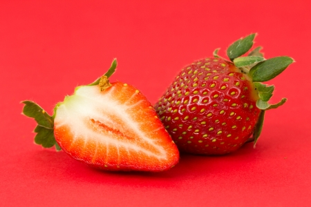Red strawberries fruit isolated on red background photo