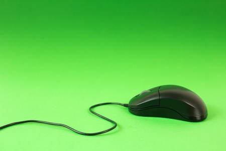 Black computer mouse on green background with cord showing