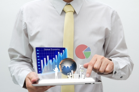 Business man holding tablet pc with graph, chart, pie, globe and building are flying off the screen Stock Photo