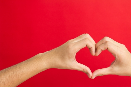 shaping: Hands in the shape of heart isolated on red background