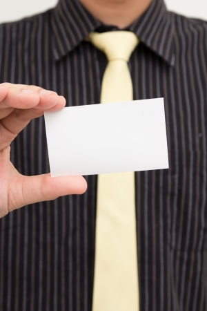 Business man holds up a blank white business card Stock Photo - 14310152
