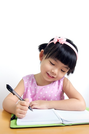 kids writing: Little kid is doing her home work with smiling face