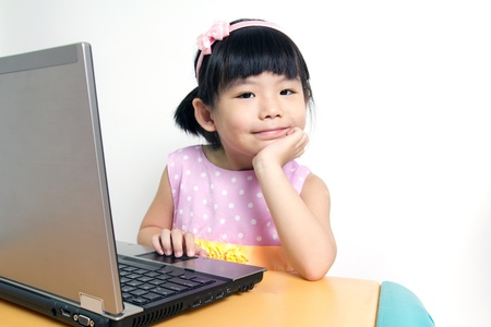 Little child girl is using laptop computer