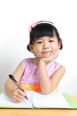 niños escribiendo: Niño pequeño que está haciendo su trabajo a casa con cara sonriente