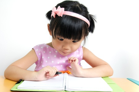 kids writing: Little kid is looking at her book surprisingly