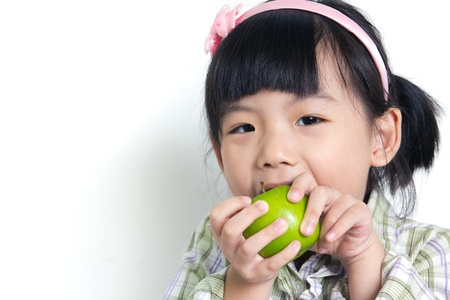 Little Asian child poses with green apple photo