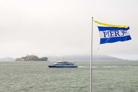 Flag of Pier 39 in San Francisco and the island of alcatraz and boat in the background