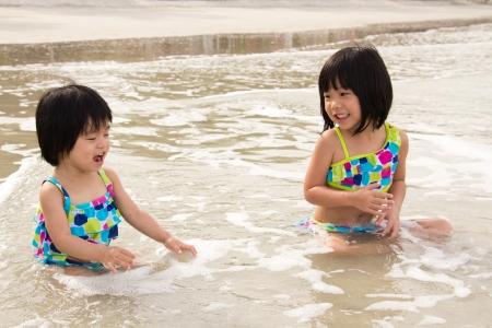 Two happy children enjoy waves on beach photo