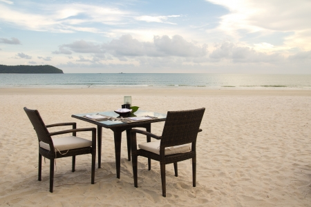 Eettafel voorbereid voor twee op wit zandstrand in de buurt van de oceaan