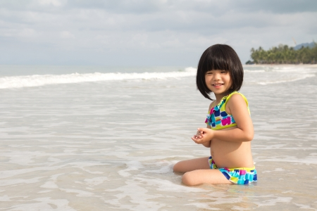 Portrait of child girl playing water on beach photo
