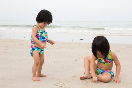 Two little girls plays sand on beach