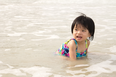 Little child girl enjoy waves on beach Stock Photo - 14722654