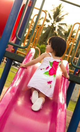 niños en area de juegos: El niño juega en la diapositiva en un patio al aire libre