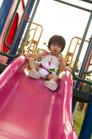 play ground: Child plays on slide in an outdoor playground