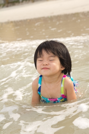 Little child girl enjoy waves on beach photo