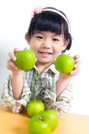 작은 아시아 아이 녹색 사과와 함께 포즈