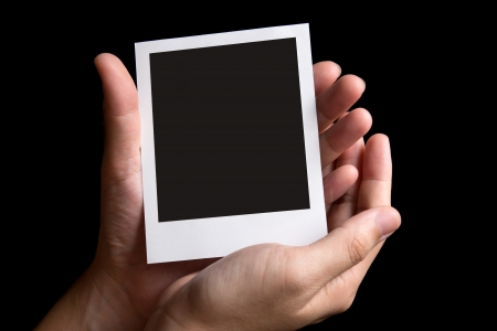 negativity: Blank instant photo frame in palm isolated in black background