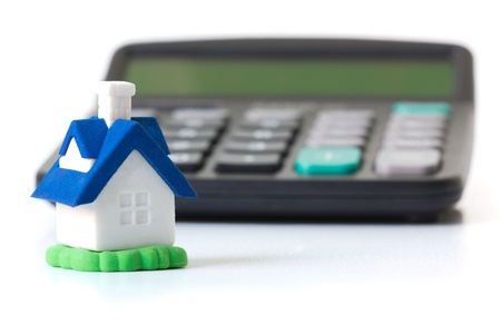 Miniature house in front of calculator concept for mortgage, home finances or saving for a house photo