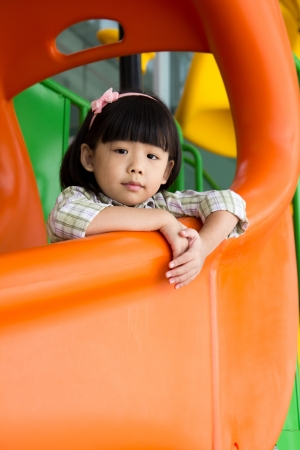 asian toddler: Child plays on slide at an indoor playground