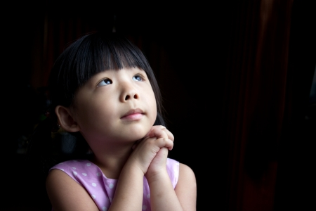 child praying: Little child is making a wish isolated in dark background