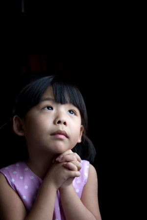 ni�o orando: Peque�o ni�o est� haciendo un deseo aislado en fondo oscuro