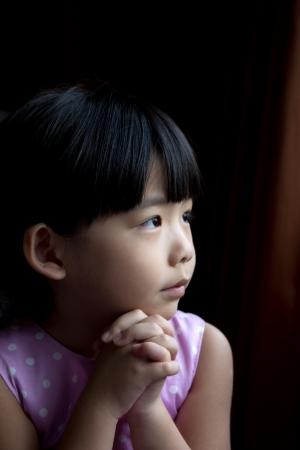 niño orando: Pequeño niño está haciendo un deseo aislado en fondo oscuro