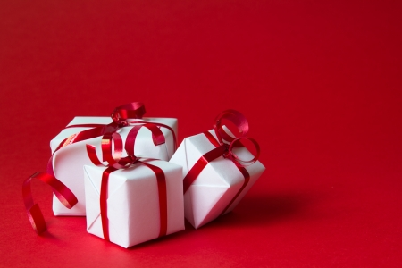 presents: White gift box with red ribbon isolated on red color background