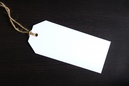 lugagge: Blank white tag on dark wooden background