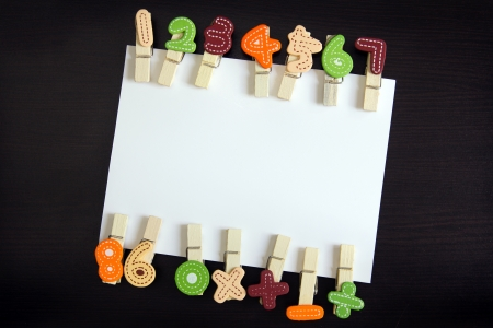 multiply: White blank card surrounded by clothespin in black wooden background Stock Photo