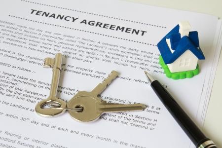 Mietvertrag, Schlüssel und Stift mit symbolischen Miniatur-Haus