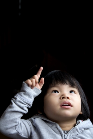 Portrait of little baby girl in curiosity isolated in dark background photo