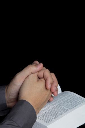 Praying hands with holy bible in dark background photo