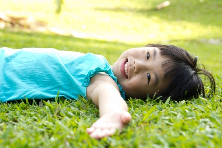 左側の庭の草の上に横たわるアジアの子供の肖像画