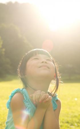 personas orando: Niño asiático está haciendo desear en el parque de la luz solar