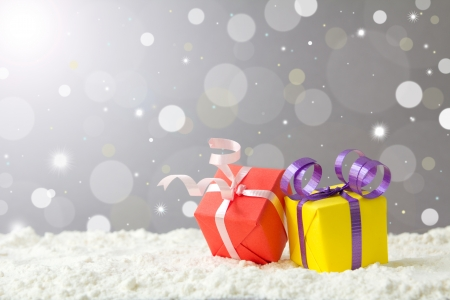 Christmas gift boxes on snow against defocused lights background photo