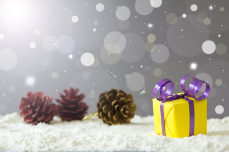 Christmas gift box on snow against defocused lights background photo