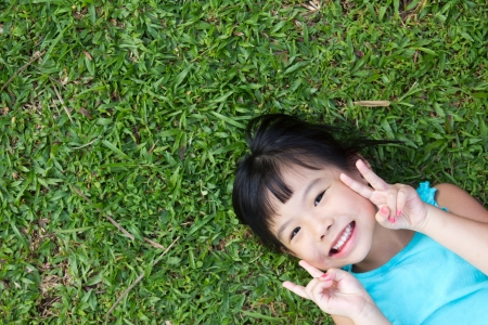Portrait of Asian child lying on garden grass looking up photo