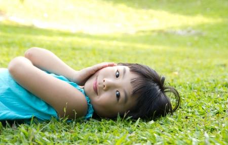 lying in grass: Retrato de ni�o acostado sobre el lado asi�tico jard�n c�sped buscando Foto de archivo