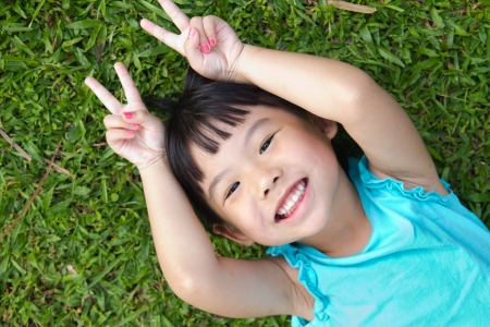 kid smiling: Portrait of Asian child lying on garden grass looking up
