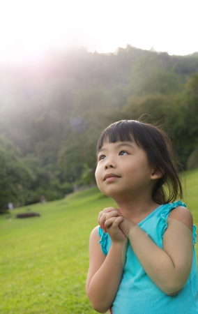 Asian child is making wish at park against sunlight