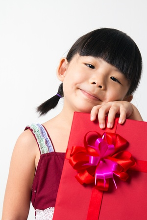 Portrait of Asian child girl with red gift box represents Christmas theme
